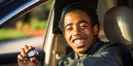 College graduate in a car holding car keys
